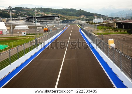 SOCHI, RUSSIA - SEPTEMBER 28, 2014: Line of championship Formula 1 in Sochi in Olimpic park against main tribune and Caucasus mountains. Preparation of competition to be held on 12 October 2014 - stock photo