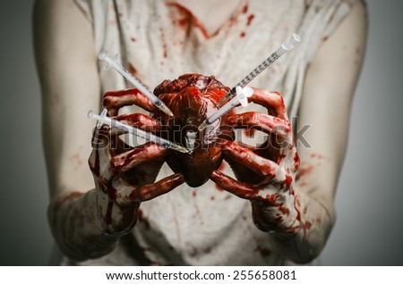 Social advertising and the fight against drug addiction: bloody hands addict holding syringe and bloody human heart - stock photo