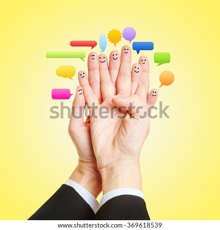 Social Media Chat with many smileys on fingers of two hands - stock photo