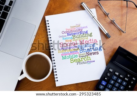 Social Media cloud words on notebook with a cup of coffee, calculator, spectacle and laptop on desk - stock photo