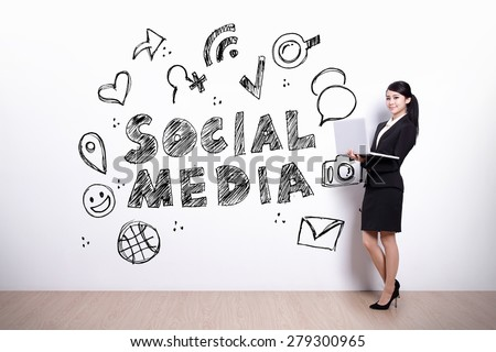 Social Media concept - business woman using laptop computer with social media text and icon on the white wall background - stock photo