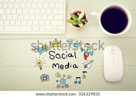 Social Media concept with workstation on a light green wooden desk - stock photo