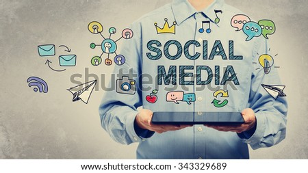 Social Media concept with young man holding a tablet computer  - stock photo
