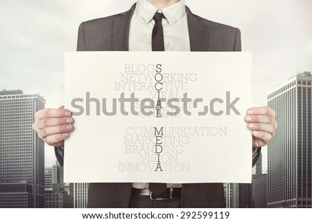 Social media crossword concept on paper what businessman is holding on cityscape background - stock photo