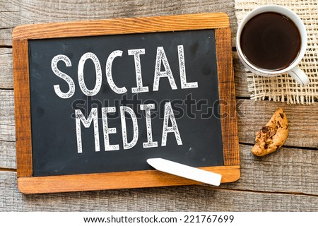 Social Media handwritten with white chalk on a blackboard, cup of coffee and biscuit on a wooden background  - stock photo