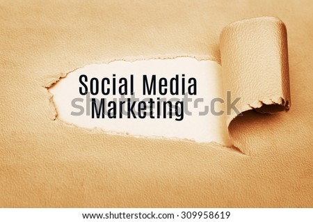 Social Media Marketing concept  written behind torn paper - stock photo