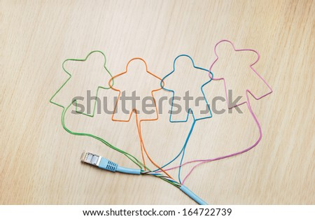 Social networking. Ethernet cable shaping silhouettes of virtual users - stock photo