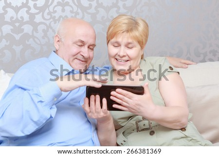 Social networking for all generations. Happy senior man and woman couple sitting together at home on a sofa using a tablet computer - stock photo