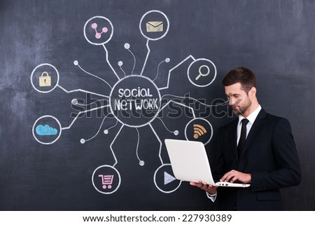 Social networking. Handsome young man working on laptop while standing against social network chalk drawing on blackboard - stock photo