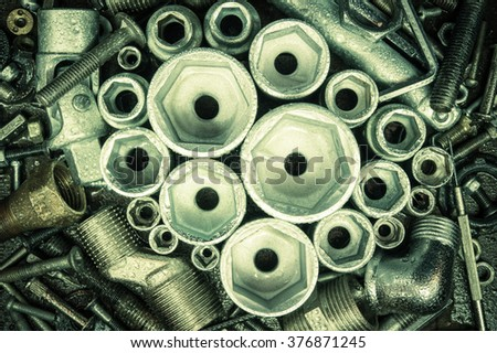 Socket spanner heads, nuts and bolts on a dark metal background.  - stock photo