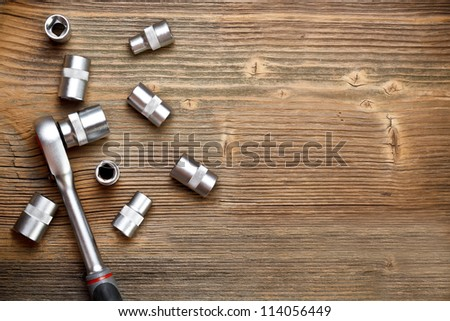 Socket spanner wrench on wood background - stock photo