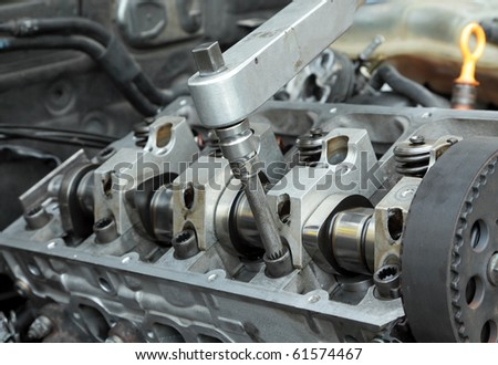 Socket wrench and camshaft of  car engine in close up