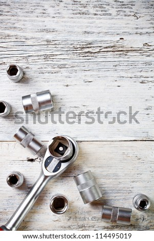 Socket wrench on painted wood background - stock photo