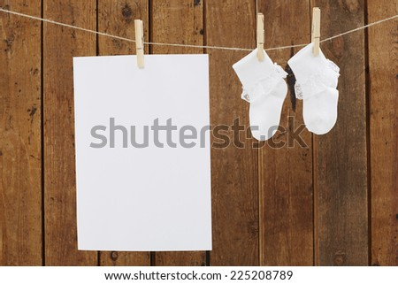 Socks and blank page on washing line - stock photo