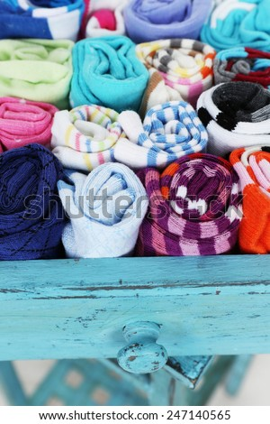 Socks in color drawer on wooden floor background - stock photo