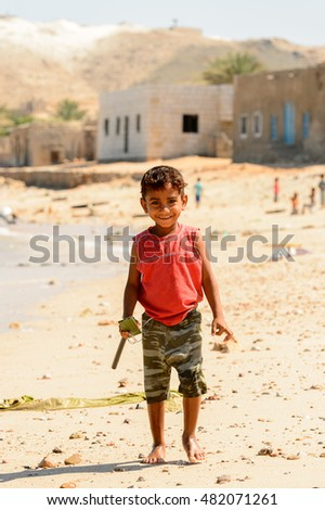 SOCOTRA, YEMEN - JAN 12, 2014: Unidentified Yemeni little boy plays on the beach of the Island of Socotra. Children in Socotra live in poverty and grow without education