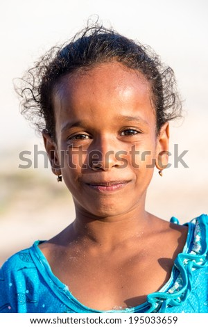 SOCOTRA, YEMEN - JAN 12, 2014: Unidentified Yemeni little girl portrait on  the beach of the Island of Socotra. Children in Socotra live in poverty and grow without education