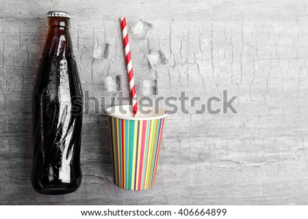 Soda bottle, ice and cup on wooden table - stock photo