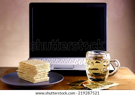 Soda Crackers, cup of tea and a computer Photo of a stack of soda crackers, cup of tea and a computer - stock photo