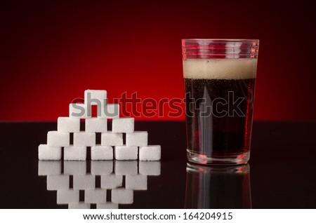 soda with bubbles in a glass, next to a pyramid of sugar cubes - stock photo