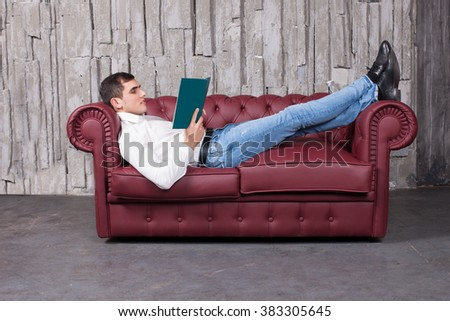 Sofa and man.Handsome guy on the couch, the background dark - stock photo