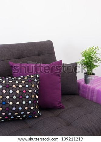Sofa decorated with colorful cushions, and green plant on side table. - stock photo