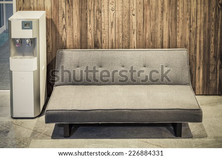 sofa furniture and water cooler on wood texture background - stock photo