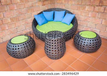 sofa furniture weave Rattan stick chair with blue pillows on orange tile and old brick wall - stock photo