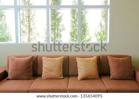 sofa in the living room with plant outside the windows - stock photo