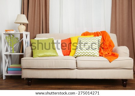 Sofa with colorful pillows in room - stock photo
