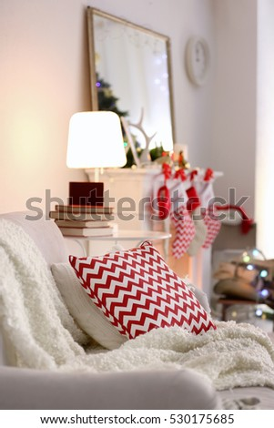 Sofa with plaid and cushion on blurred background, close up view