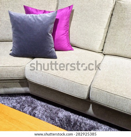 Sofa with purple cushions and coffee table on a fluffy carpet. - stock photo