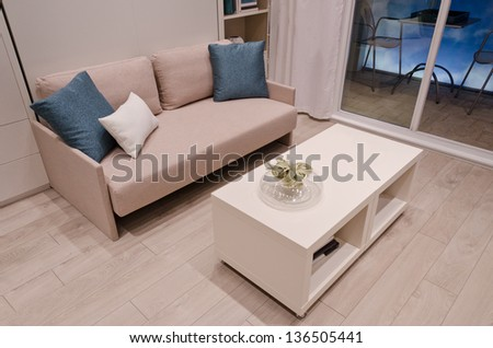 Sofa with some pillows and a coffee table. Interior design. Fragment. - stock photo