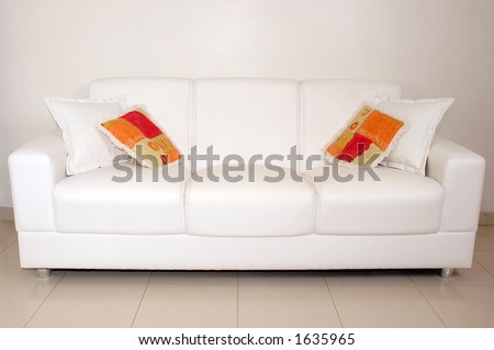 Sofa with white and colored cushions / pillows - stock photo