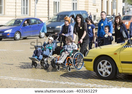 Sofia, Bulgaria - April 6, 2016: Physically and mentally disabled are accompanied by their parents, relatives and friends at a protest against policies against them. - stock photo