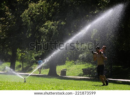 Sofia, Bulgaria - August 18, 2014: Father and son are playing with the water of the irrigation system of Borisova gradina park in Sofia. - stock photo