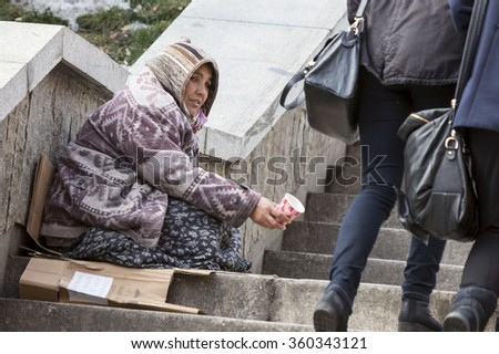Sofia, Bulgaria - January 8, 2016: A homeless gypsy woman is begging for money in the center of Sofia. Years after joining the EU the country is still struggling with poverty among its citizens - stock photo