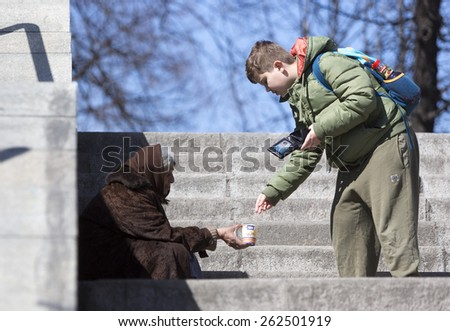 Sofia, Bulgaria - March 17, 2015: A boy is giving money to a homeless female beggar who is begging at the subway underpass stairs in the center of Sofia. - stock photo
