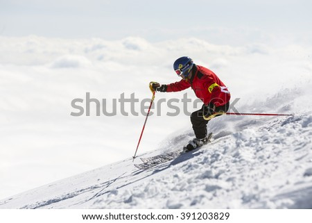 Sofia, Bulgaria - March 12, 2016: Freestyle skier is skiing at the top of a snowy peak of Vitosha mountain covered in clouds. He is participating in an freestyle competition of skiers and snowboarders - stock photo