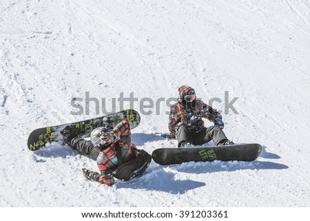Sofia, Bulgaria - March 12, 2016: Two teenage snowboarders are sitting on the ski slope just before a freestyle competition for skiers and snowboarders begins. - stock photo