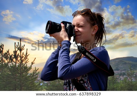 SOFIA, BULGARIA - MAY 08, 2017: Young girl photography beatutiful nature sunset scene with her Canon camera and lens. Selective focus on canon text near her shoulder
