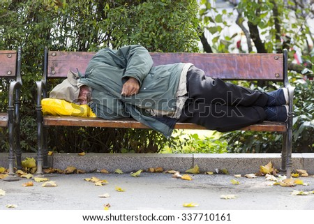 Sofia, Bulgaria - October 28, 2015: Homeless person is sleeping on a bench in a cold autumn day in a park in European union's poorest country Bulgaria. - stock photo