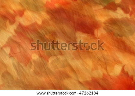 Soft abstract background image of fall foliage.  Photo of leaves in motion layered with textured paper.