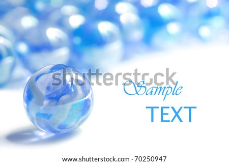 Soft abstract image of blue marbles on white background with copy space. Macro with extremely shallow dof. - stock photo