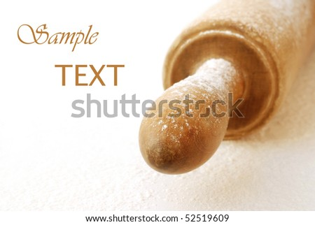 Soft abstract image of wooden rolling pin dusted with flour on white background.  Macro with extremely shallow dof. - stock photo