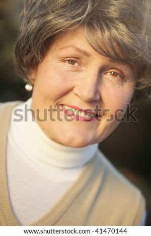 Soft and luminous portrait of a beautiful older lady - stock photo
