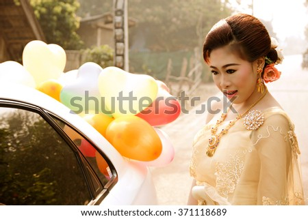 Soft Beautiful Thai women wearing typical Thai dress, identity culture of Thailand, looking at self reflection in mirror car - stock photo