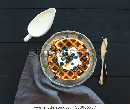 Soft Belgian waffles with blueberries, honey and whipped cream on vintage metal plate over black wooden background, top view - stock photo