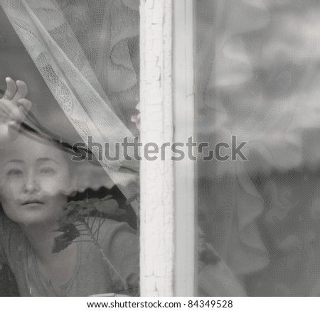 soft black and white portrait of Asian woman behind the window glass - stock photo