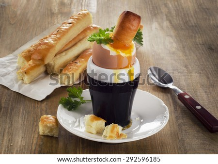 Soft boiled egg for Breakfast  served with bread on   a rustic wooden table. Selective focus - stock photo